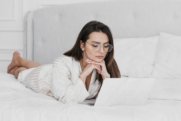 Donna piena del colpo che lavora a letto con il computer portatile