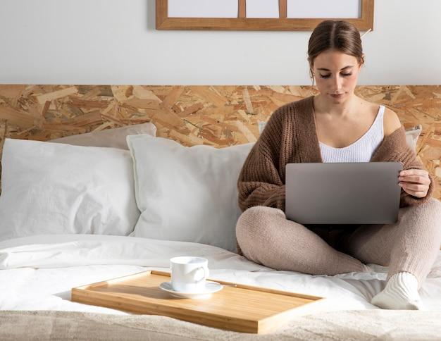 Donna piena del colpo che lavora nella camera da letto