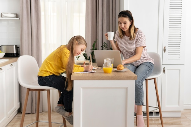 Full shot woman working at home with girl
