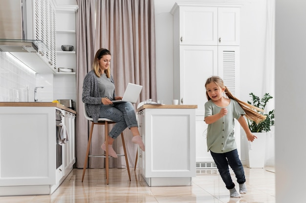 Full shot woman working at home with kid