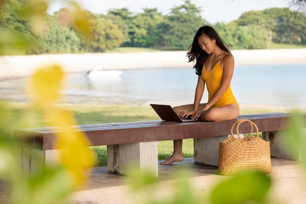 Full shot woman working on laptop outdoors