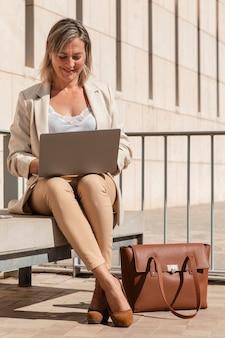 Donna piena del colpo che lavora al computer portatile