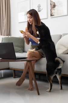自宅でラップトップに取り組んでいるフルショットの女性