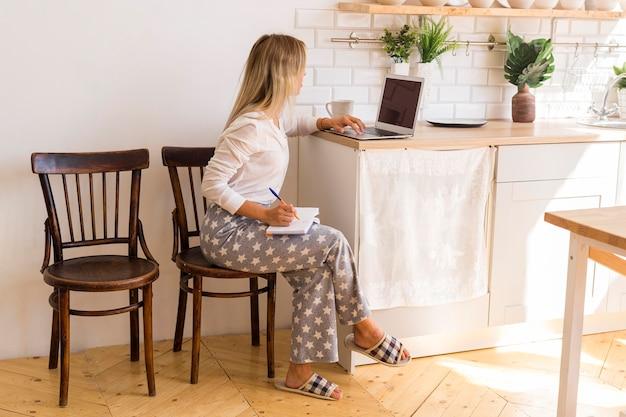 Полный выстрел женщина, работающая на ноутбуке