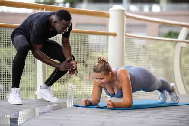トレーナーと一緒に運動するフルショットの女性