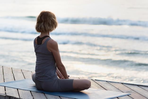Donna piena del colpo sulla stuoia di yoga di fronte al mare