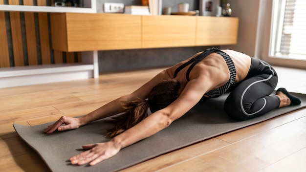 Full shot woman on yoga mat stretching
