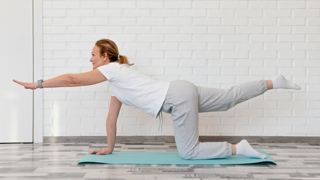Full shot woman on yoga mat