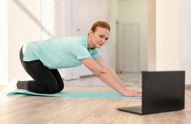 Donna piena del colpo sulla stuoia di yoga