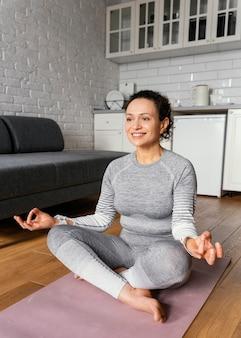 Donna piena del colpo sul materassino yoga