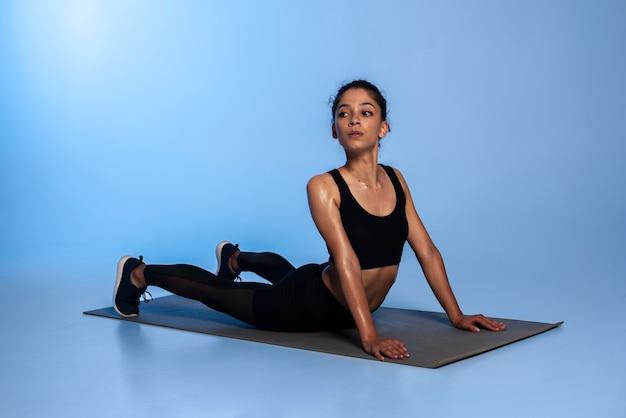 Donna a tutto campo sul tappetino da yoga