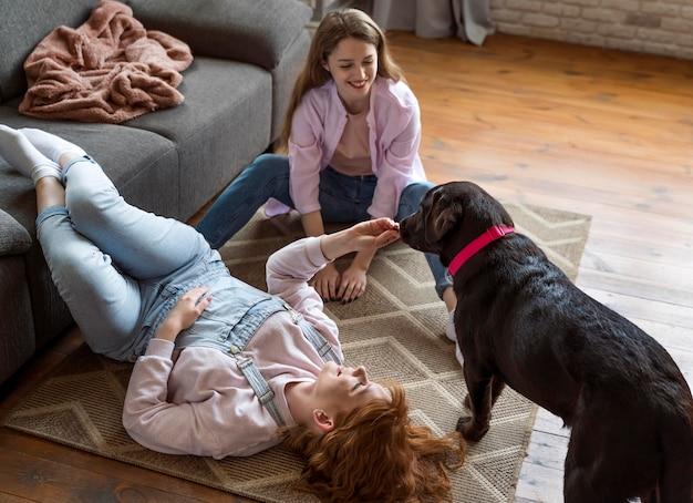フルショットの女性と犬が床に横たわっています