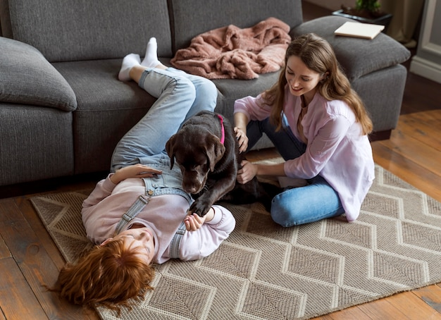 フルショットの女性とカーペットの上の犬