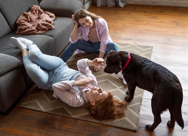Полный снимок женщины и собаки на полу