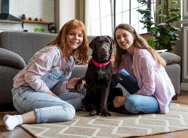 フルショットの女性と犬が床でポーズをとる