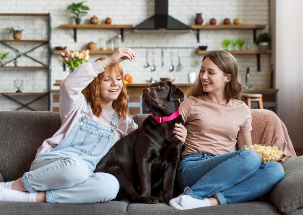 フルショットの女性とソファに座っている犬