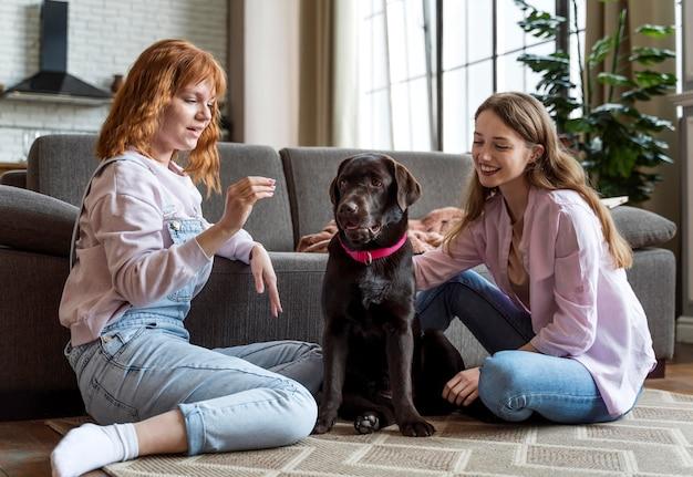 フルショットの女性とおやつを持つ犬