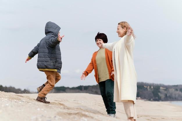 해변에서 풀 샷 여자와 아이