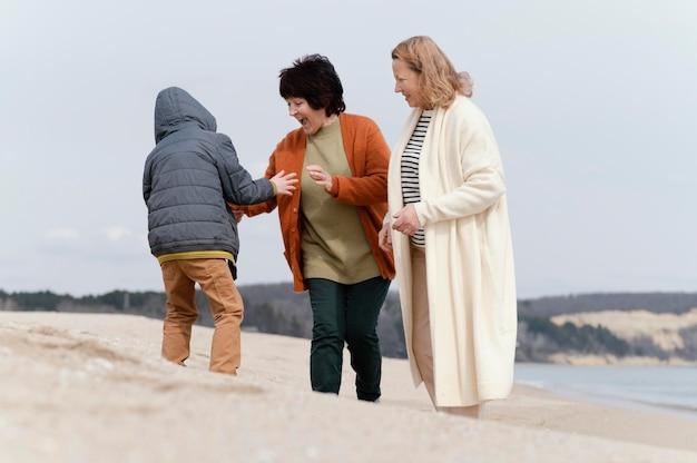 海辺のフルショットの女性と子供