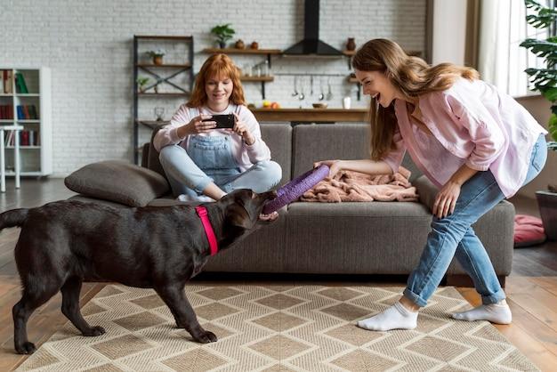 Full shot donne e cane che giocano gioco