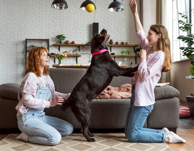 Donne e cane del colpo pieno che giocano insieme