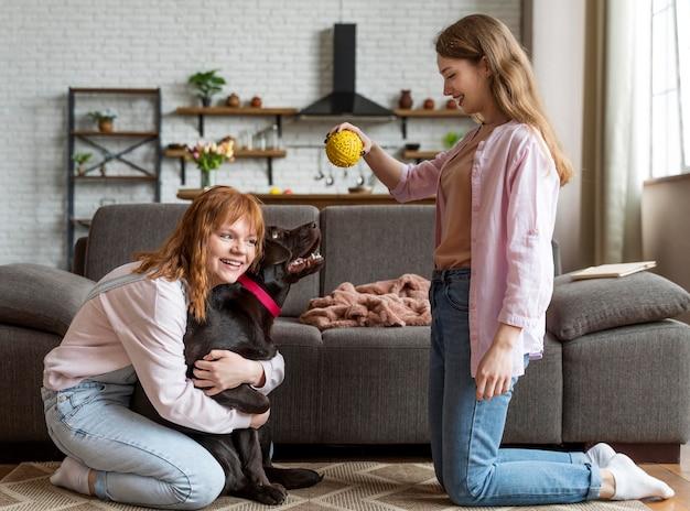 Donne del colpo pieno e cane che giocano con la palla