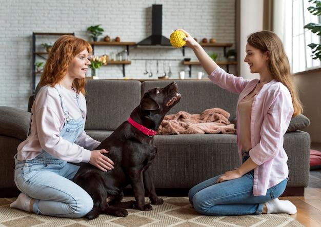 Donne e cane pieno del colpo che giocano con il giocattolo