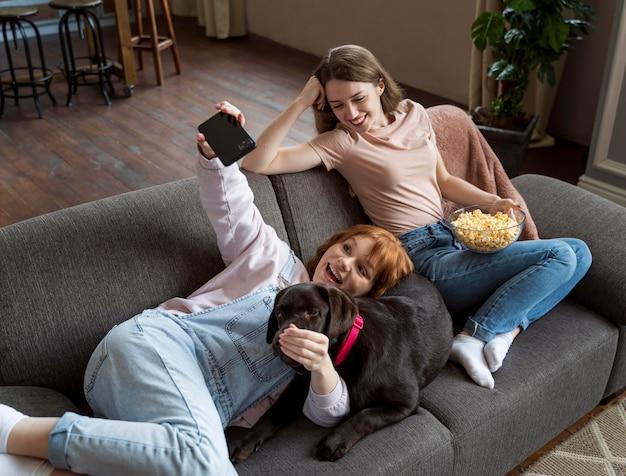 Full shot donne e cane che prendono selfie