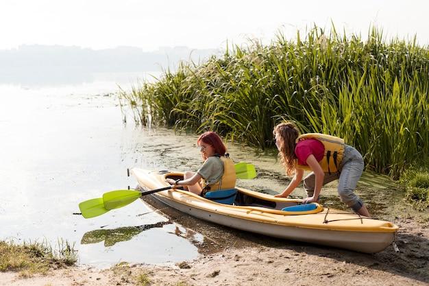 Full shot women getting kayak out of water