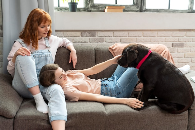 Full shot women laying on couch with dog