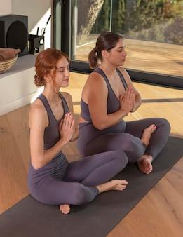 ヨガマットで瞑想するフルショットの女性
