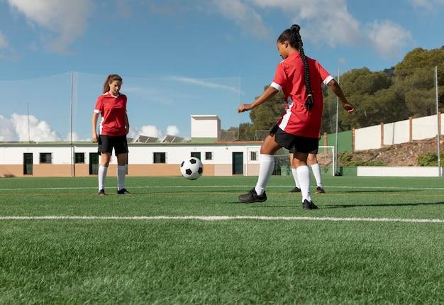 Полный выстрел женщин, играющих в футбол