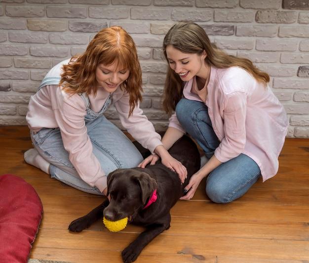 Donne del colpo pieno che giocano con il cane sul pavimento