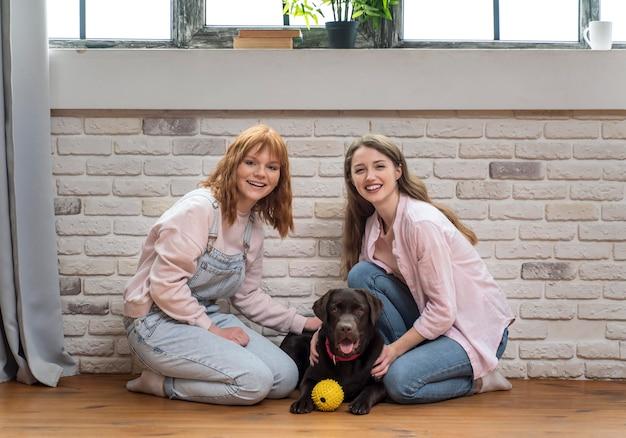 犬とポーズをとるフルショットの女性
