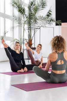 Full shot women practicing yoga together