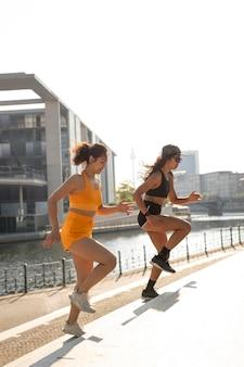 Full shot women running on stairs