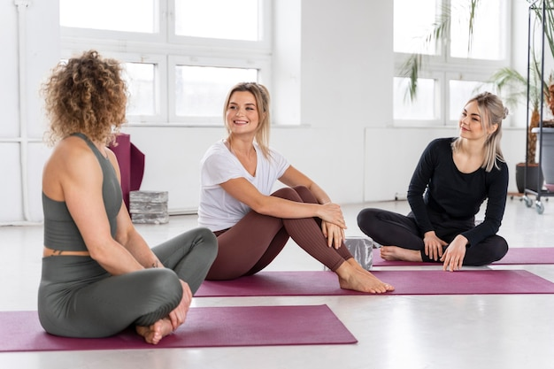 Full shot women sitting on mats