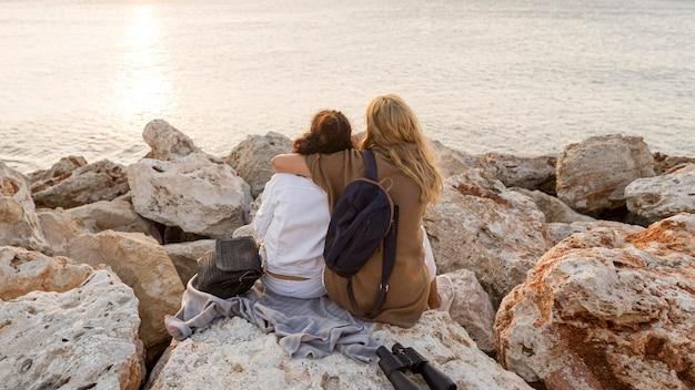 Full shot women sitting on rock