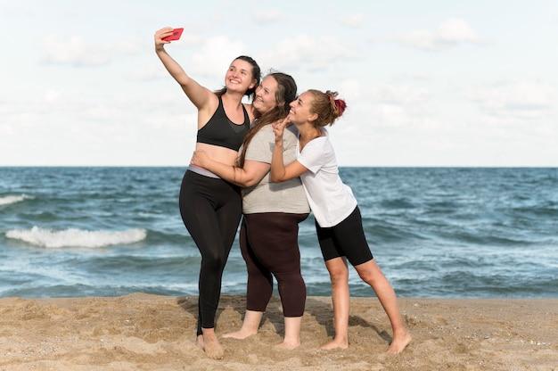 海辺でselfiesを取るフルショットの女性