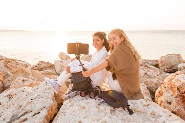 Donne del colpo pieno che prendono insieme i selfie