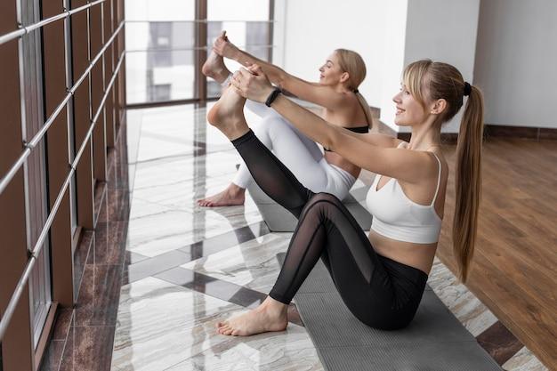 Donne del colpo pieno che si allenano sul materassino yoga