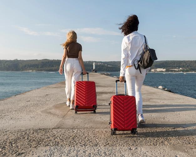Full shot women traveling with luggage