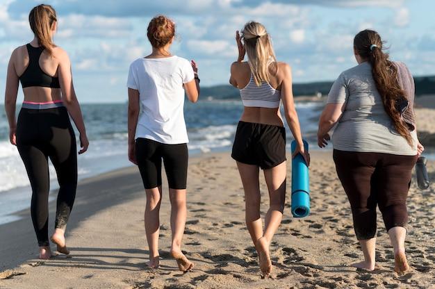 Donne del colpo pieno che camminano sulla riva