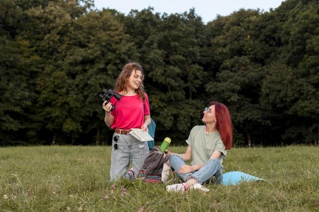 Полный снимок женщин с биноклем, стоящих на траве и улыбающихся