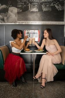 Donne del colpo pieno con hamburger e patatine fritte