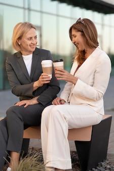 屋外でコーヒーカップを持つフルショットの女性