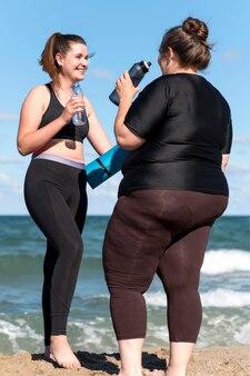 水のボトルを持つフルショットの女性