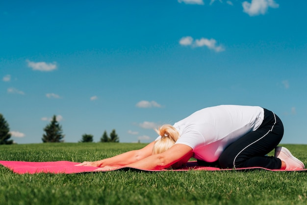 Full shot yoga posture on mat outdoors