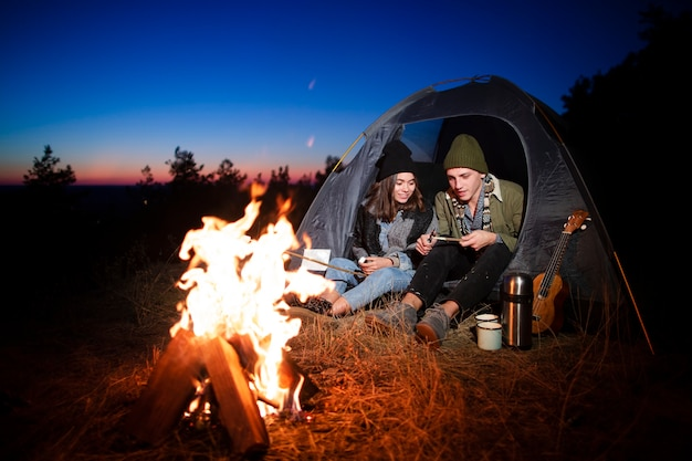 Full shot young couple with bonfire