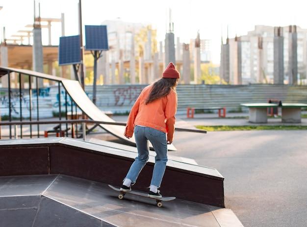 Молодая девушка в полный рост на коньках на открытом воздухе